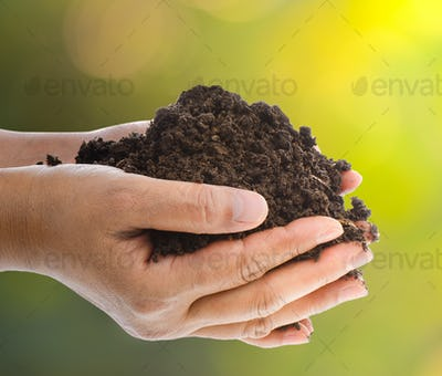 Handful of black soil over nature  background