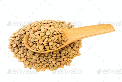 lentils in wood spoon isolated on white background