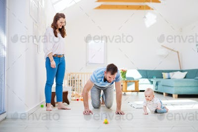 Young family playing with a baby boy at home.