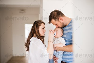 Young family with a baby boy drinking from a plastic bottle at home.