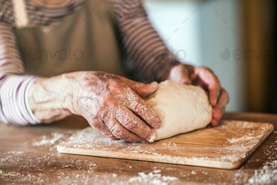 An unrecognizale senior woman kneading dough in the kitchen at home.