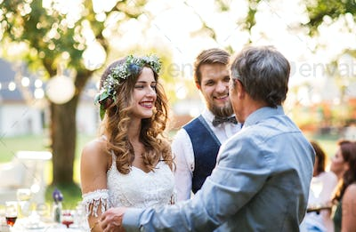 A father congratulating bride and groom at wedding reception in the backyard.