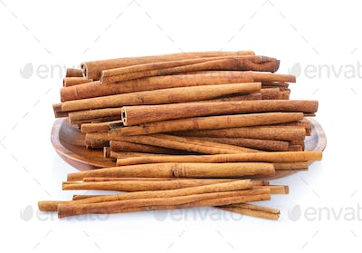 Cinnamon in plate on white background
