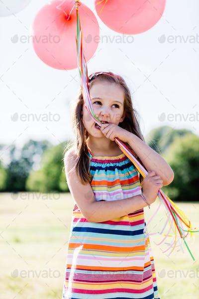 Little girl chewing balloon strings in her mouth
