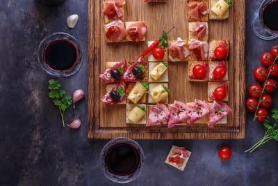 Close view of small tapas topped with jamon, cured meat and cheese