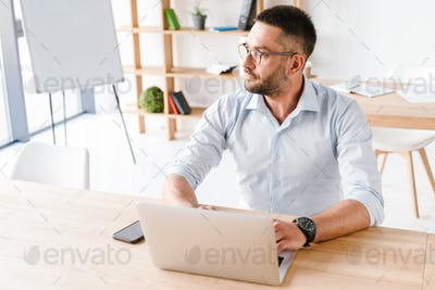 Photo of attractive office man 30s in white shirt sitting at tab