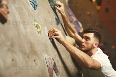 Young man climbing artificial rock wall at gym