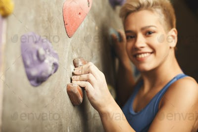 Young woman climbing artificial rock wall at gym
