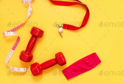 Two red dumbbells, tape measure and whistle