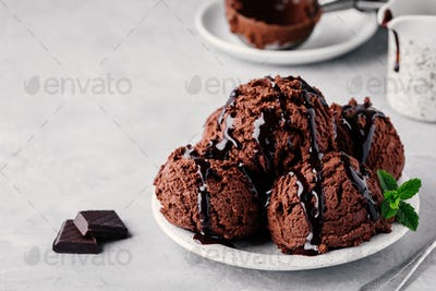A plate of chocolate ice cream scoops with chocolate sauce