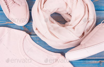 Womanly clothing and accessories on old boards, leather shoes, sweater and shawl
