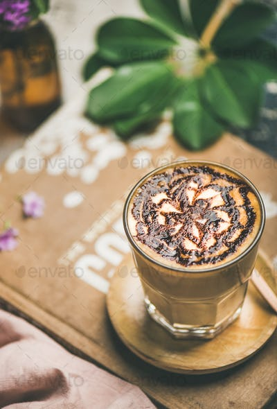 Classic Latte coffee with chocolate sauce pattern in tall glass