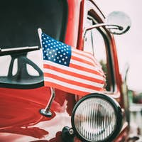 Close Side View Of Red Pickup Truck With Small American Flag Wav