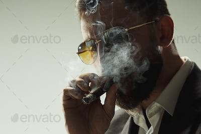 The barded man in a suit holding cigar