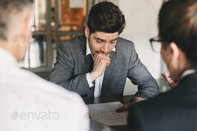 Nervous uptight man 30s worrying and biting fist during job inte