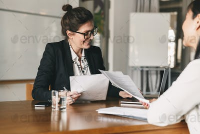 Photo of successful woman holding resume and negotiating with fe
