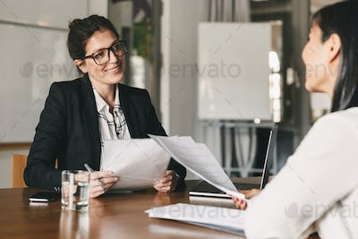 Portrait of smiling businesswoman holding resume and talking to