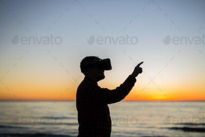 Future has come. Man wearing virtual reality goggles