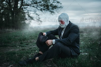 Serial maniac sitting on the ground in forest