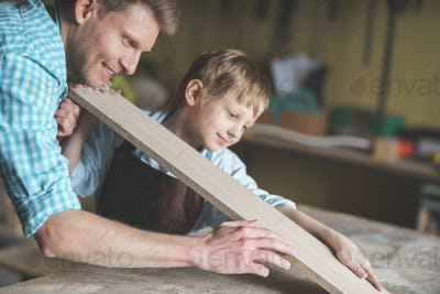 Smiling father and son in the carpentry