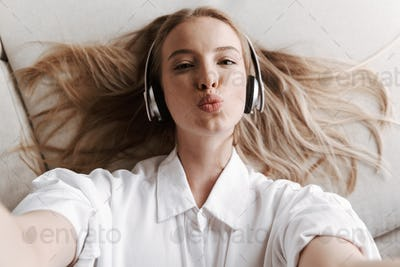 Pretty young woman indoors at home listening music