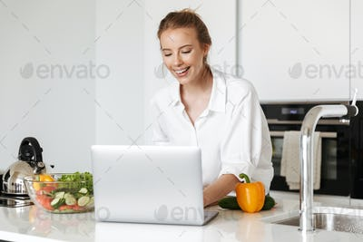 Happy young woman cooking salad