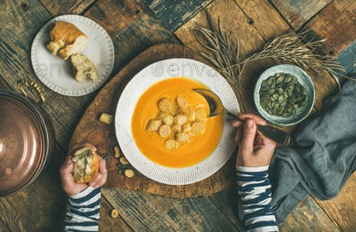 Fall warming pumpkin cream soup with seeds and bread croutons