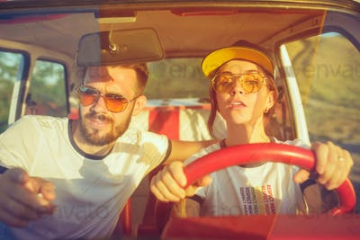 Laughing romantic couple sitting in car while out on a road trip at summer day