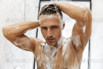 Close up of a concentrated man having a shower