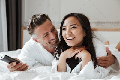 Photo of multiethnic couple caucasian man and asian woman wearin