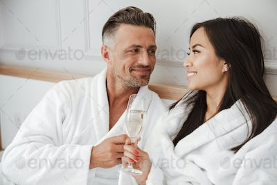 Romantic couple 30s caucasian man and asian woman wearing white