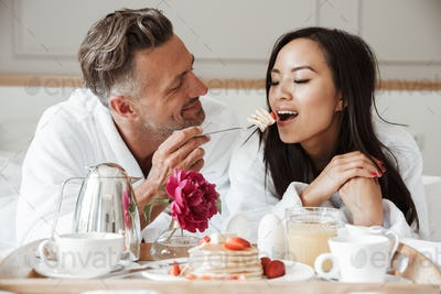 Smiling young couple dressed in bathrobes