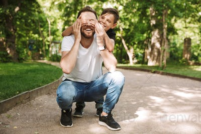 Happy little son covering eyes of his cheerful father