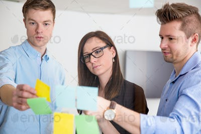 Business Colleagues Discussing Over Adhesive Notes Stuck On Glas