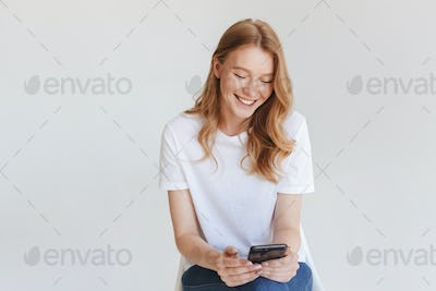 Redhead happy woman using mobile phone.