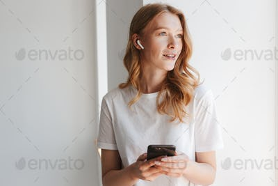 Pretty young redhead woman listening music with earphones by mobile phone.