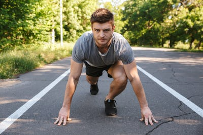 Confident sportsman ready to start running on a road