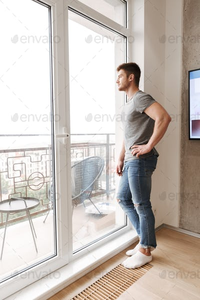 Pensive young man standing at the window