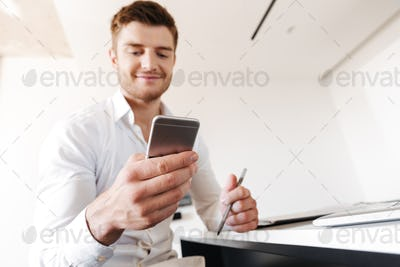 Satisfied young man using mobile phone