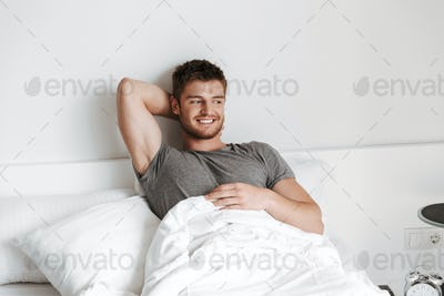 Attractive young man sitting in bed