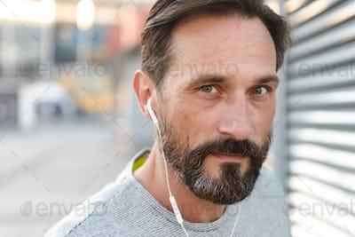 Handsome mature sportsman listening music with earphones.