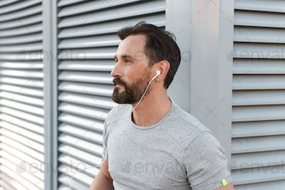 Handsome strong mature sportsman listening music with earphones.
