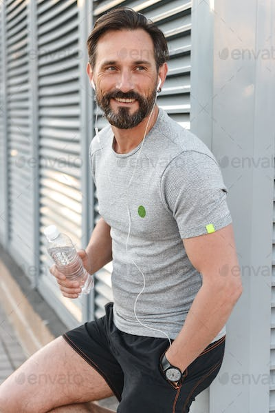 Handsome strong mature sportsman with earphones holding bottle with water.