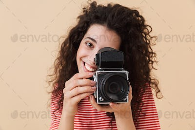 Pretty young curly woman photographer
