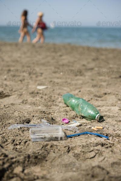 Plastic garbage left on a sandy beach.