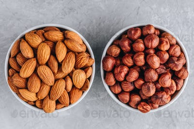 Raw almonds and hazelnuts in bowl. Top view