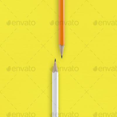 White and orange pencils on yellow background