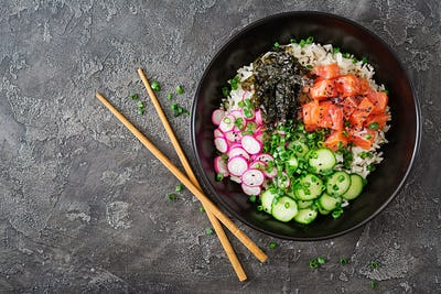 Hawaiian salmon fish poke bowl with rice, radish,cucumber, tomato, sesame seeds and seaweeds.