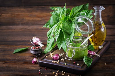 Homemade pesto sauce fresh basil, pine nuts and garlic on wooden background. Italian food.