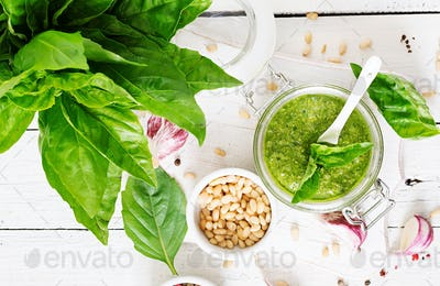 Homemade pesto sauce fresh basil, pine nuts and garlic on wooden background.